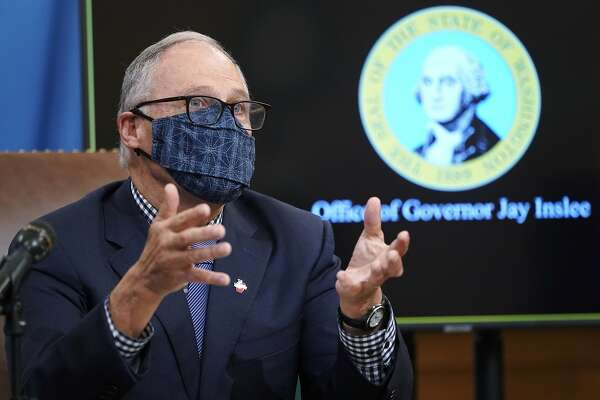 FILE - In this Dec. 17, 2020 file photo, Washington Gov. Jay Inslee talks to reporters at the Capitol in Olympia, Wash. State lawmakers across the country will be convening in 2021 with the continuing COVID-19 pandemic rippling through much of their work - and even affecting the way they work. After 10 months of emergency orders and restrictions from governors and local executive officials, some state lawmakers are eager to reassert their power over statewide decisions shaping the way people shop, work, worship and attend school (AP Photo/Ted S. Warren, File)