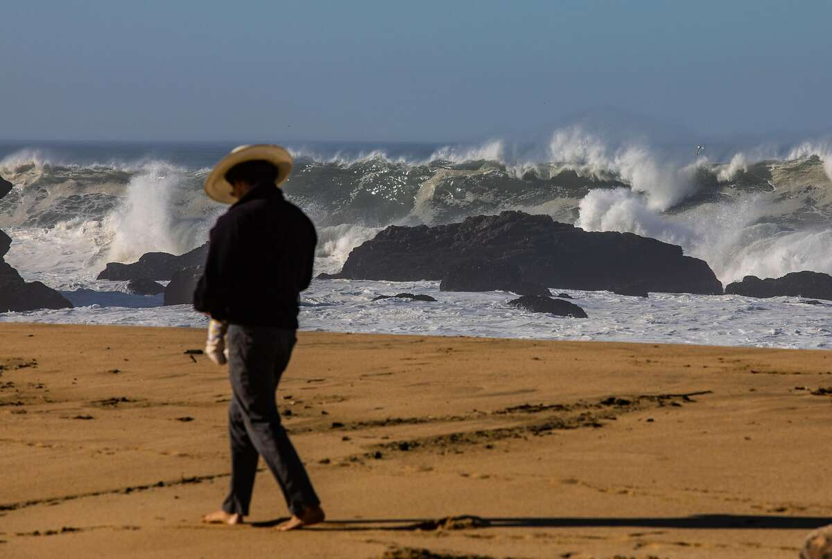 Beachgoers watch the huge swell at Montara State Beach in Montara, Calif. The National Weather Service issued a high surf warning as massive waves crashed against the Bay Area coastline on Tuesday, Dec. 8, 2020. In addition to another round of rainfall set to fall Wednesday, the NWS again warned of sneaker waves along Bay Area coasts.