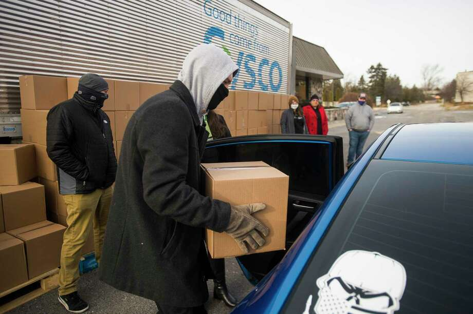 Mark Miracle of Bay City places a box of food into a vehicle as volunteers distribute the food boxes, donated by Sysco of Michigan, to hospitality workers and their families in a drive-through format Tuesday afternoon at Valley Lanes in Midland. The event was one of several give-aways throughout the state organized by Sysco of Michigan, The Michigan Restaurant & Lodging Association Educational Foundation and The Michigan Hospitality Industry Employee Relief Fund. (Katy Kildee/kkildee@mdn.net)