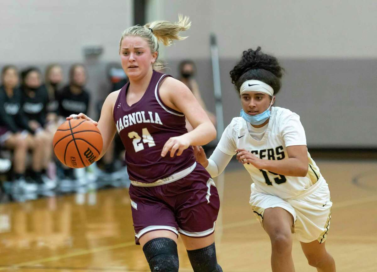 Magnolia's Claire McCusker (24) drives the ball while under pressure from Conroe's Daniela Galindo (15) during the second quarter of a non-district game in Porter Gym at Conroe High School, Tuesday, Dec. 29, 2020, in Conroe.