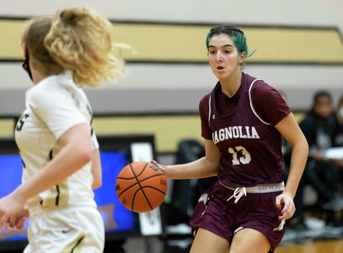Magnolia's Gabrielle Huetter (13) looks for an opening to pass the ball during the second quarter of a non-district game in Porter Gym at Conroe High School, Tuesday, Dec. 29, 2020, in Conroe.