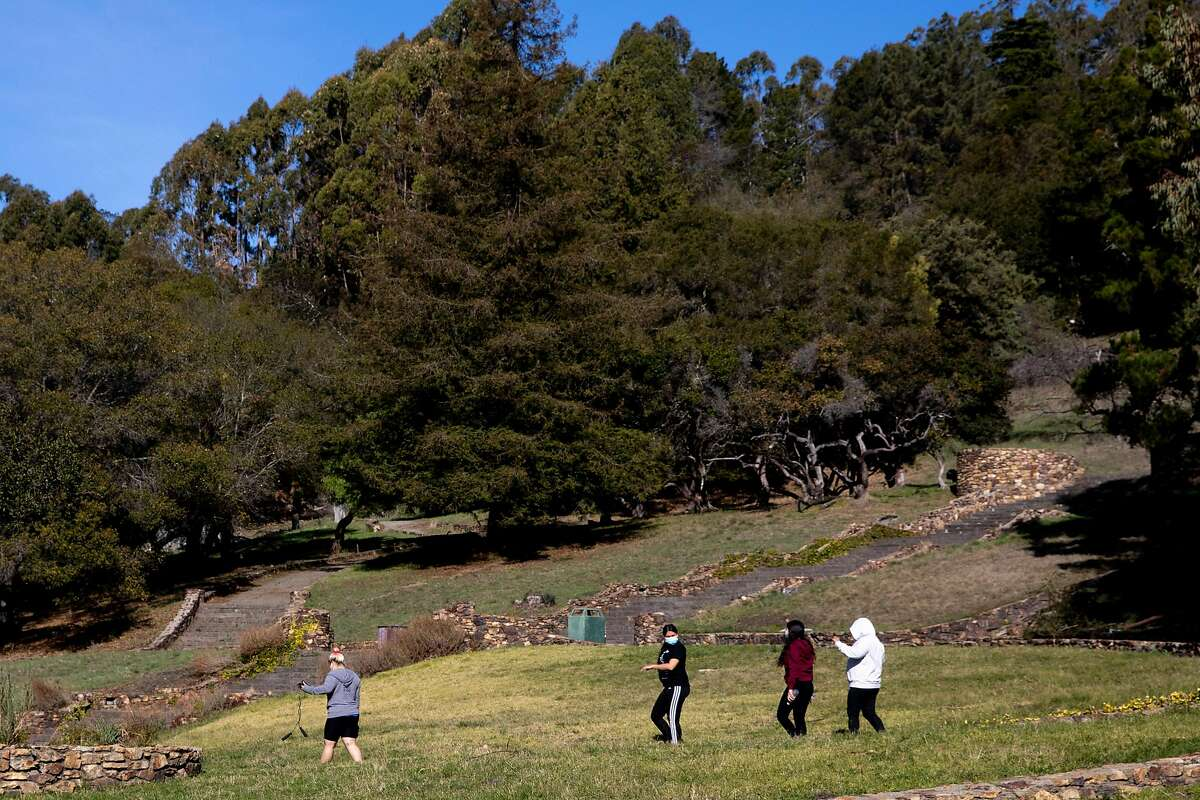 A group of friends wear masks while walking along a trail at Joaquin Miller Park in Oakland, Calif. Tuesday, December 29, 2020. Rain is forecasted to gather over the Bay Area in later this week.