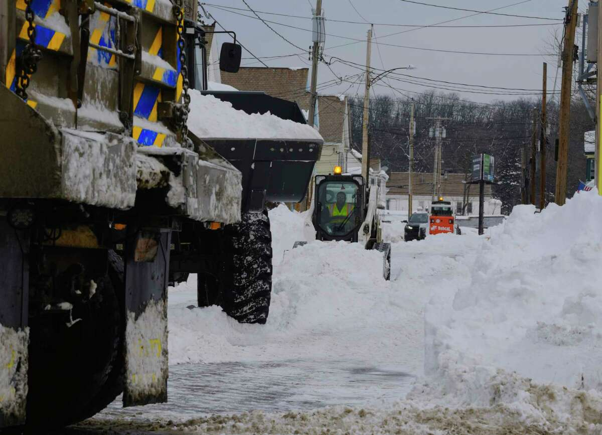 Crews work to remove snow from Edward St. on Sunday, Dec. 20, 2020, in Schenectady, N.Y. New York State Department of Transportation dump trucks were used to haul the snow away. (Paul Buckowski/Times Union) ORG XMIT: ALB2012201641280001