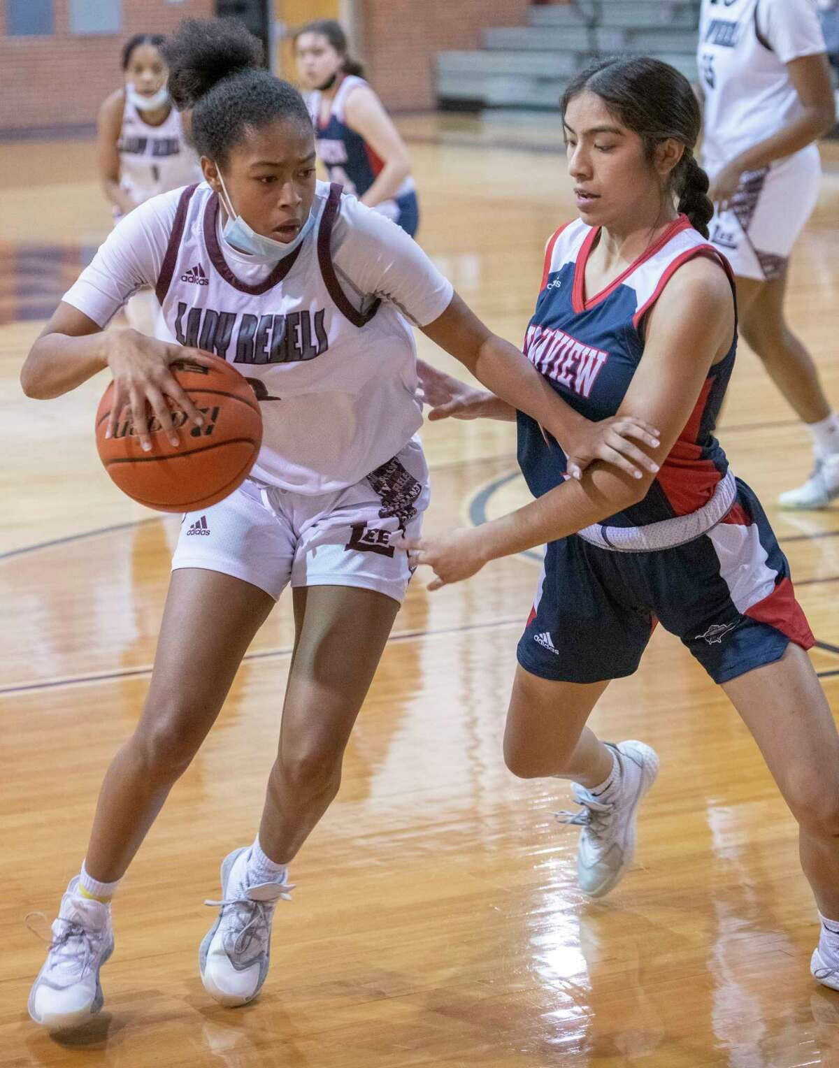 Lee High's Sa'Nya Green tries to go inside as Plainview's Zay Santos defends 12/29/2020 at the Lee High gym. Tim Fischer/Reporter-Telegram