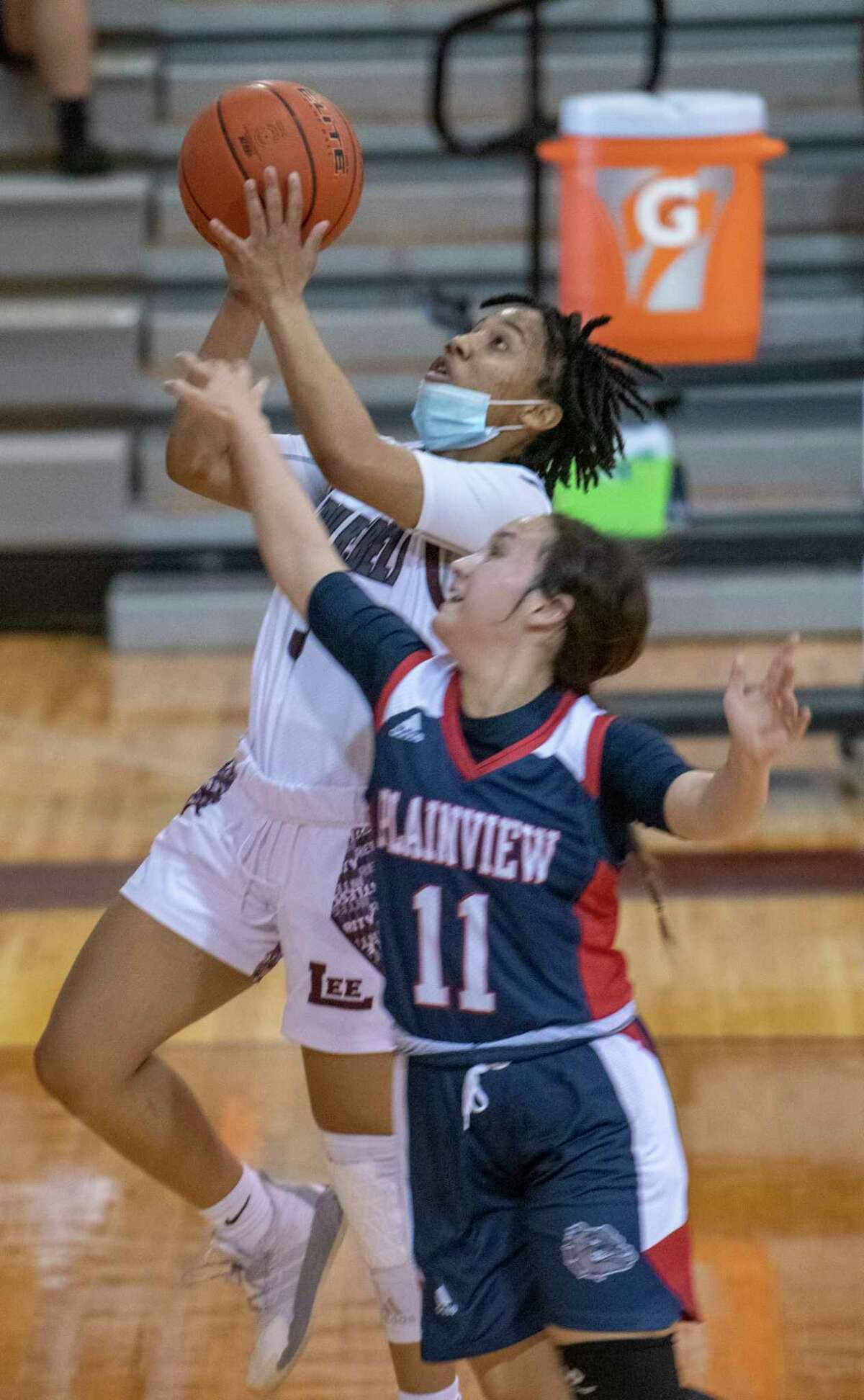 Lee High's Alyssa Green drives to the basket as Plainview's Emily Sigala defends 12/29/2020 at the Lee High gym. Tim Fischer/Reporter-Telegram