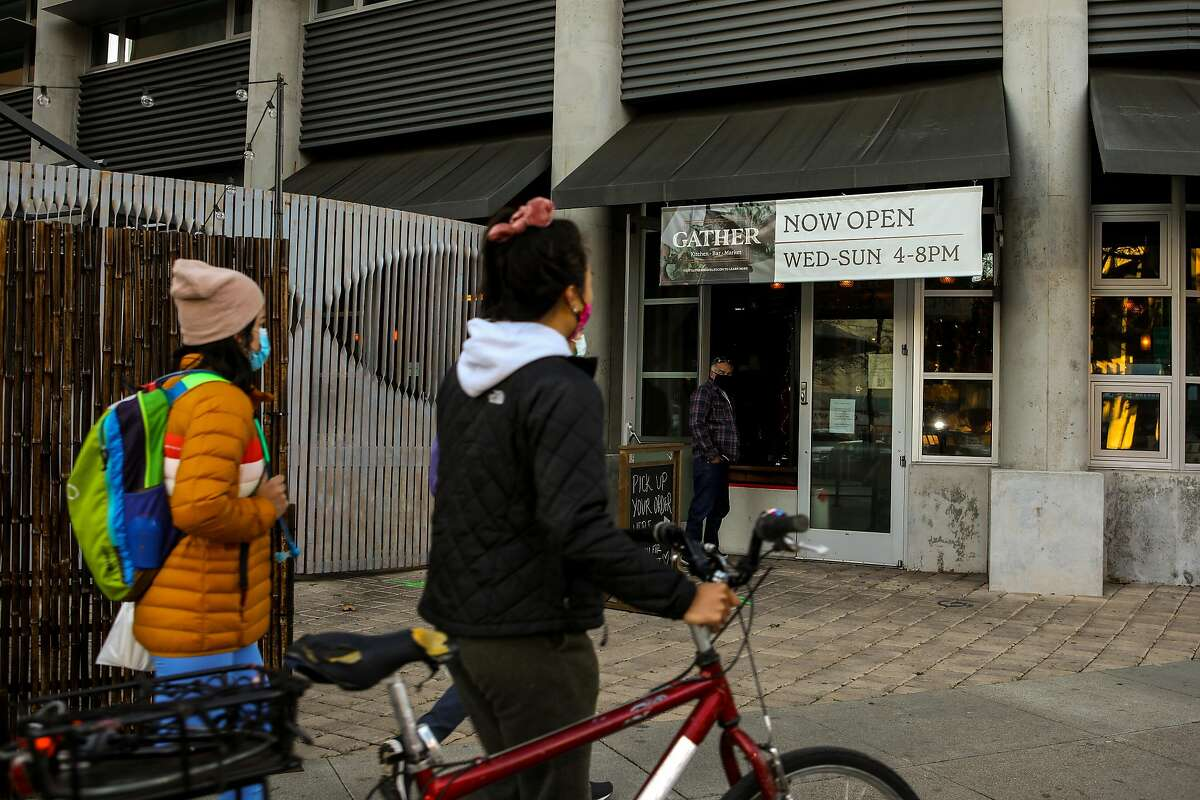 People stop outside Gather Kitchen, Bar & Market, which has had to switch to takeout during the pandemic.