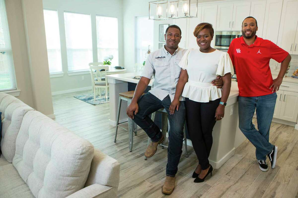 Kevan and Ayesha Shelton, left, and Junious Williams pose for a portrait in one of the homes they have built in the Grand Park Square development Thursday, Nov. 12, 2020 in Houston. Shelton is developing homes in the Greater South Union area. Grand Park Square is meant to to inspire a new sense of community and drive to preserve and maintain the culture in the area as gentrification threatens other historic, underserved neighborhoods.
