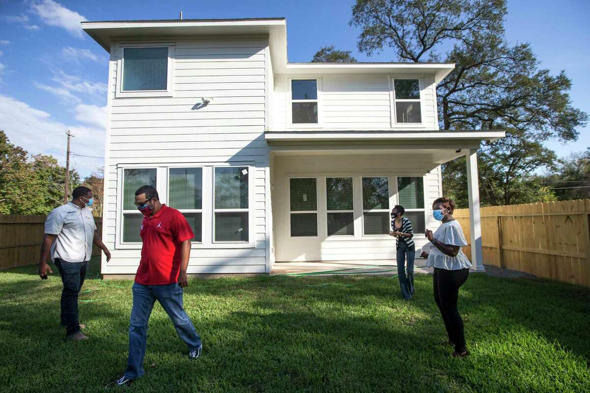 Kevan Shelton, left, Junious Williams IV, Dana Hewling and Ayesha Shelton walk through the back yard of one of the homes they have recently built in the Grand Park Square development Thursday, Nov. 12, 2020 in Houston. Shelton is developing homes in the Greater South Union area. Grand Park Square is meant to to inspire a new sense of community and drive to preserve and maintain the culture in the area as gentrification threatens other historic, underserved neighborhoods.