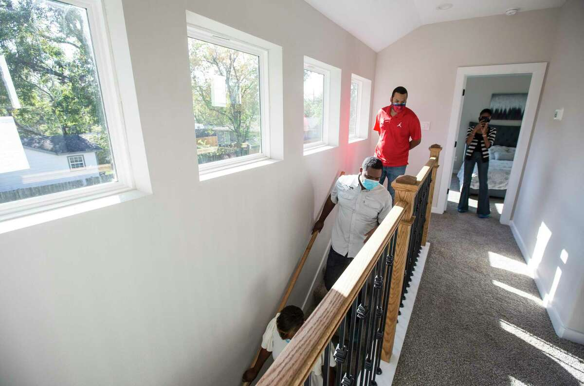 Ayesha Shelton, Kevan Shelton and Junious Williams walk down the stairs in one of the homes they have built in the Grand Park Square development Thursday, Nov. 12, 2020 in Houston. Shelton is developing homes in the Greater South Union area. Grand Park Square is meant to to inspire a new sense of community and drive to preserve and maintain the culture in the area as gentrification threatens other historic, underserved neighborhoods.