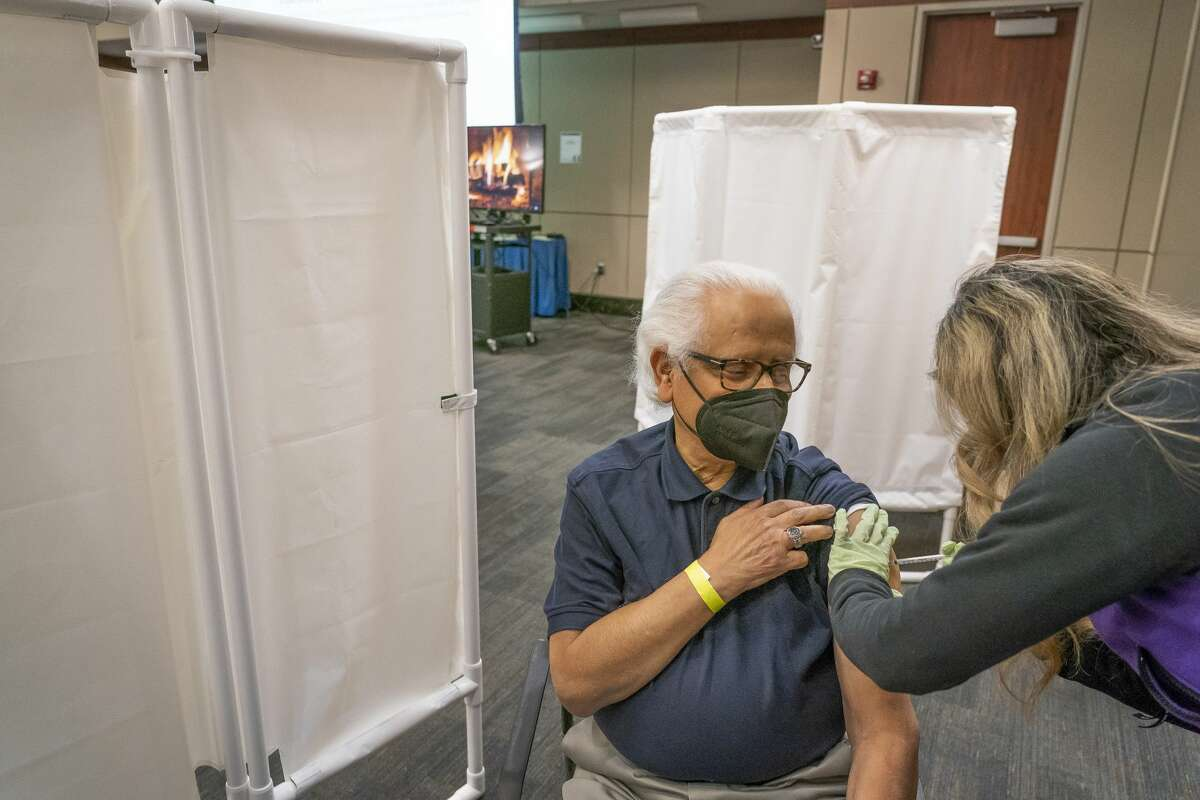Manoj Biswas, 79, a retired OBGYN, receives his first dose of the Pfizer-manufactured COVID-19 vaccine from RN Lizette Coronado on Tuesday, Dec. 29, 2020, at Houston Methodist Hospital in the Texas Medical Center. The hospital started including seniors and patients with chronic conditions in their vaccination program this week.