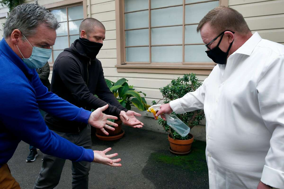 Shaween Sullivan (right) sprays hand sanitzer on people before lunch in the dining room at the Salvation Army's Harbor Light Center in San Francisco, Calif. on Wednesday, Dec. 16, 2020.