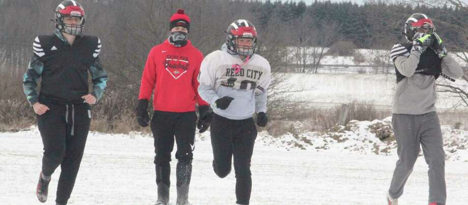 Despite all the surrounding snow, Reed City football players begin their Tuesday working on their practice field. The emphasis was social distancing with rapid testing set to occur later on Tuesday and on Wednesday. (Pioneer photo/John Raffel)