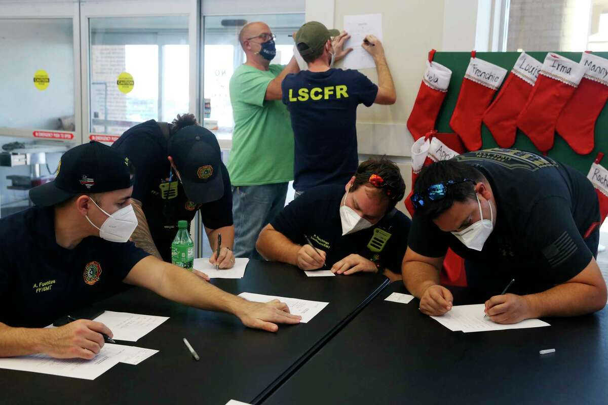 First responders with the La Salle County Fire Rescue fill out paperwork before getting the Moderna COVID-19 vaccine at Frio Regional Hospital in Pearsall, Texas, Wednesday, Dec. 23, 2020. It is one of almost half of all Texas rural hospitals with that have gotten or are on the list for the COVID-19 vaccine. The hospital got 300 doses and was able to also vaccinate La Salle County Fire Rescue first responders.