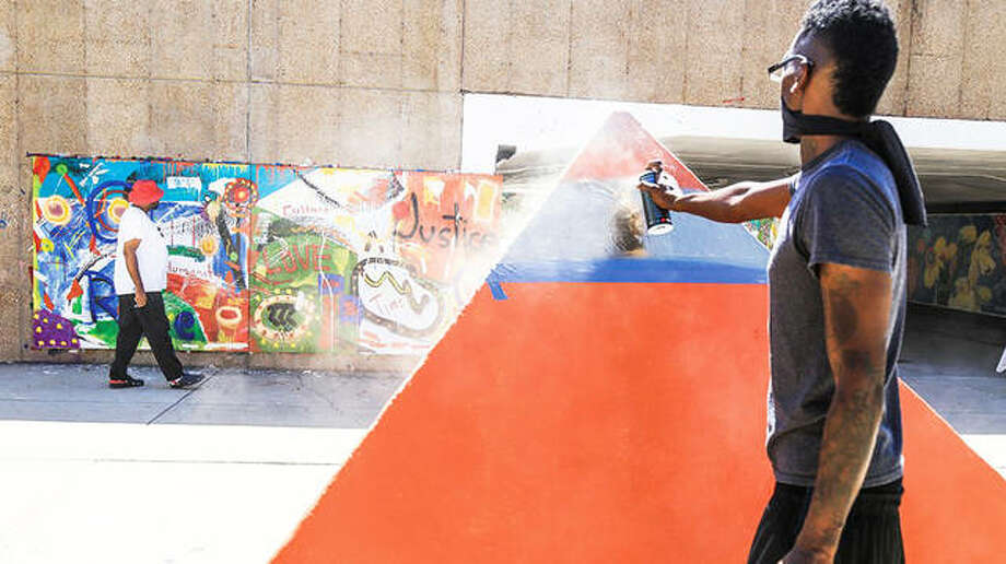 Multi-media artist De'Joneiro Jones, background, 46, of St. Louis, walks some of the 6-foot-by-6-foot panels of a 2020-styled public art mural for which he was commissioned at the South 40 Underpass on Washington University's Danforth Campus in St. Louis. One of Jones' five recruited mentees, Roland Burrow, forefront, paints a pyramid at the site of the mural, completed last summer under Jones' supervision. Photo: Photo Courtesy And Permission Of De'Joneiro Jones | For The Telegraph