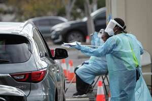 A Covid-19 testing site staff member gives a self-swabbing kit to a driver at the Minute Maid location for free COVID-19 testing Tuesday, Dec. 29, 2020, in Houston.
