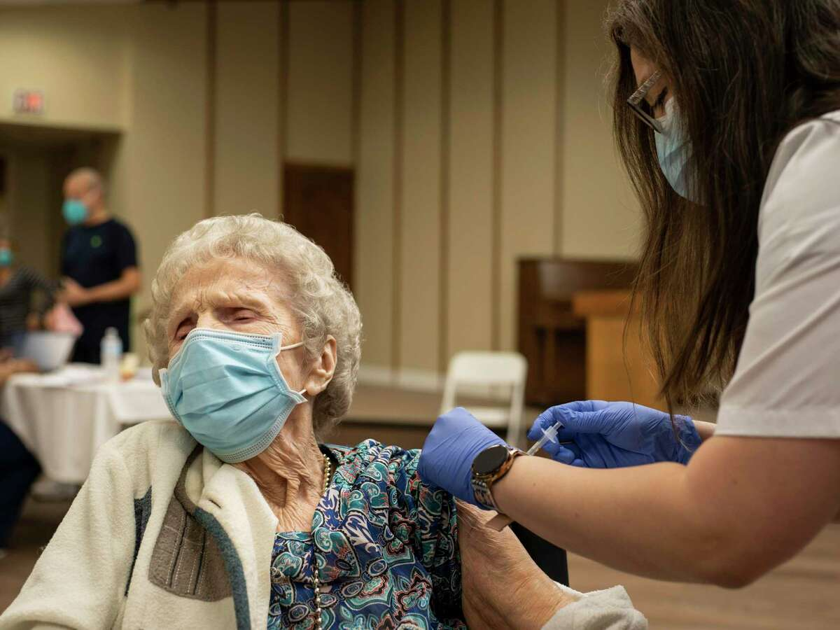 Ora Lee Mair, 92, a resident at Morningside at the Meadows assisted living facility looks away as she receives the Pfizer-BioNTech COVID-19 vaccine from CVS pharmacist intern Gabriela Alfaro, right, Tuesday.
