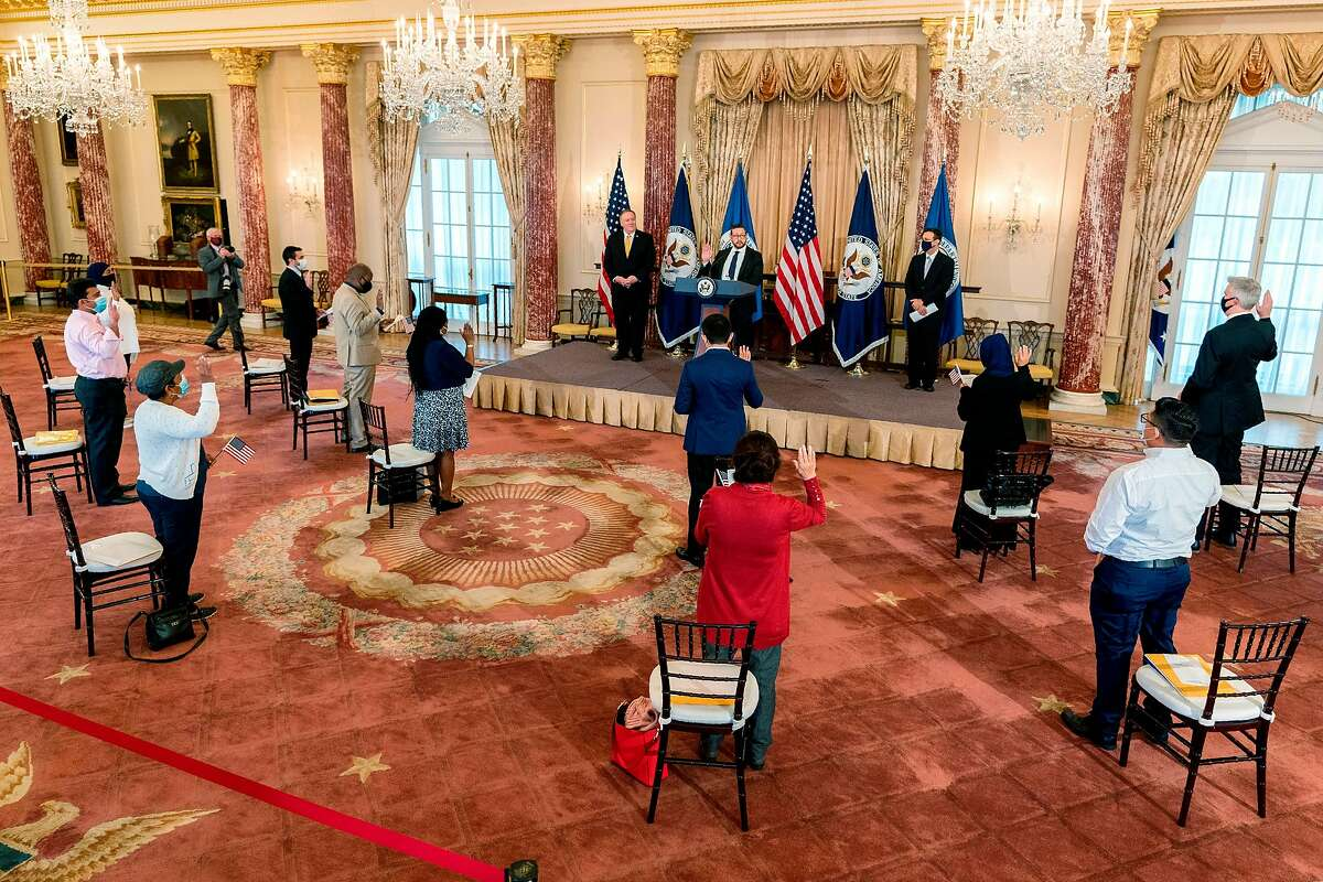 Joseph Edlow (center rear) of U.S. Citizenship and Immigration Services, with Secretary of State Mike Pompeo (left rear), administers the oath of allegiance to 12 candidates for citizenship during an October naturalization ceremony in Washington.