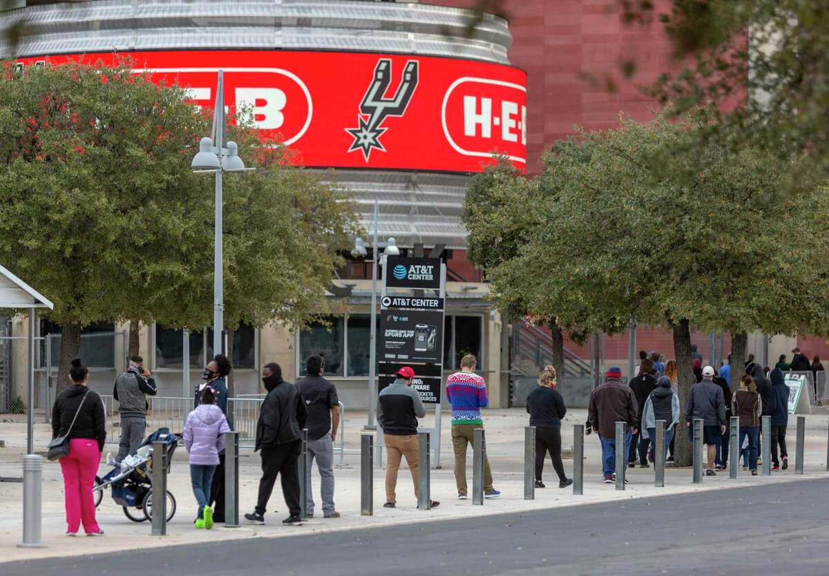 People wait in line outside the AT&T Center on Dec. 29 to get a coronavirus test the day after COVID case numbers forced area businesses to reduce their occupancy capacities to from 75 to 50 percent.
