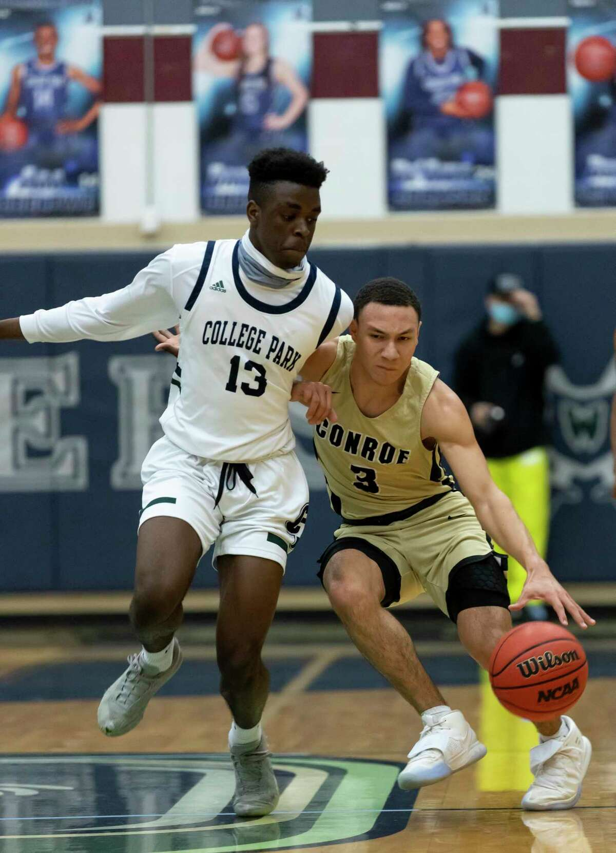 Conroe Mikey Sneed (3) pushes against College Park small forward Ellis Ibizugbe (13) as he drives the ball during the first quarter of a District 13-6A boys basketball game at College Park High School, Tuesday, Dec. 29. 2020, in The Woodlands.