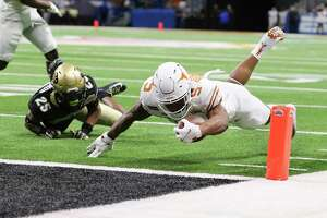 Texas RB Bijan Robinson dives past Colorado's Luke Stillwell for a first-quarter touchdown at the Alamo Bowl. Robinson added a receiving score later in the quarter.