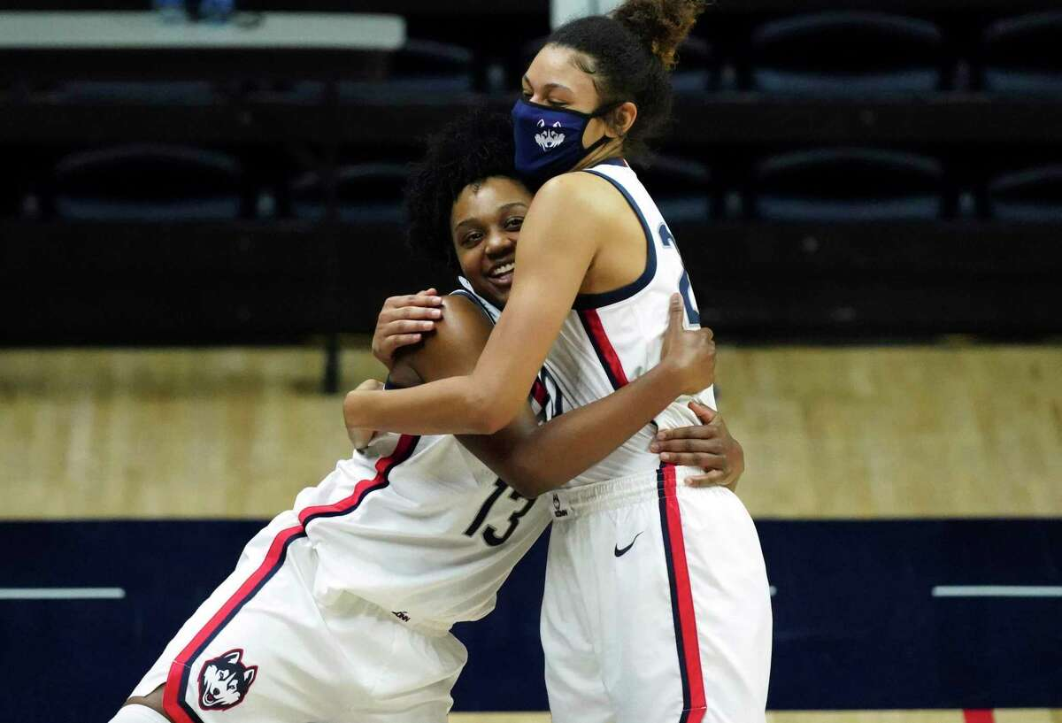 Connecticut guard Christyn Williams (13) hugs forward Olivia Nelson-Ododa (20) as she reacts to the stadium display as family and friends congratulate her on her, after the team's win over DePaul in an NCAA college basketball game Tuesday, Dec. 29, 2020, in Storrs, Conn. (David Butler II/Pool Photo via AP)