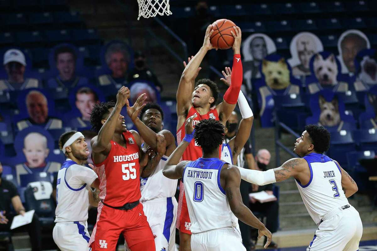 Houston's Quenton Grimes drives to the basket against Tulsa defenders, including Curtis Haywood III and Elijah Joiner during the first half of an NCAA college basketball game in Tulsa, Okla., Tuesday, Dec. 29, 2020. Houston's Brison Gresham is at left. (AP Photo/Dave Crenshaw)