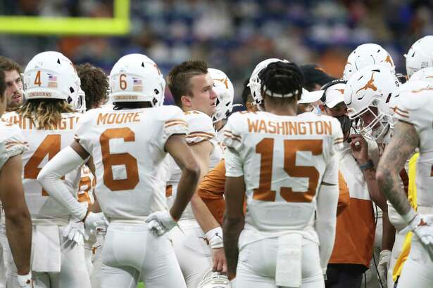Sam Ehlinger leads the huddle on the sideline as the Longhorns take a break in the first quarter as Texas plays Colorado in the Alamo Bowl at the Alamodome on Dec. 29, 2020.
