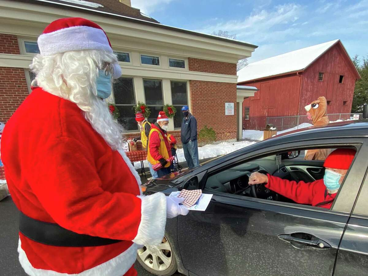 Walter Bayer, right, who is known to portray Santa in town, is greeted by another Santa Tom Williams, who hands him a Christmas card.