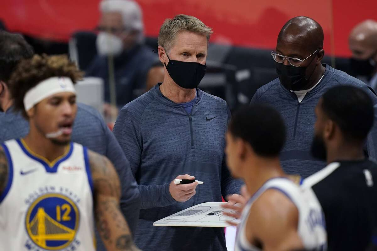 Warriors head coach Steve Kerr and lead assistant Mike Brown wear masks during a game in Detroit on Dec. 29.