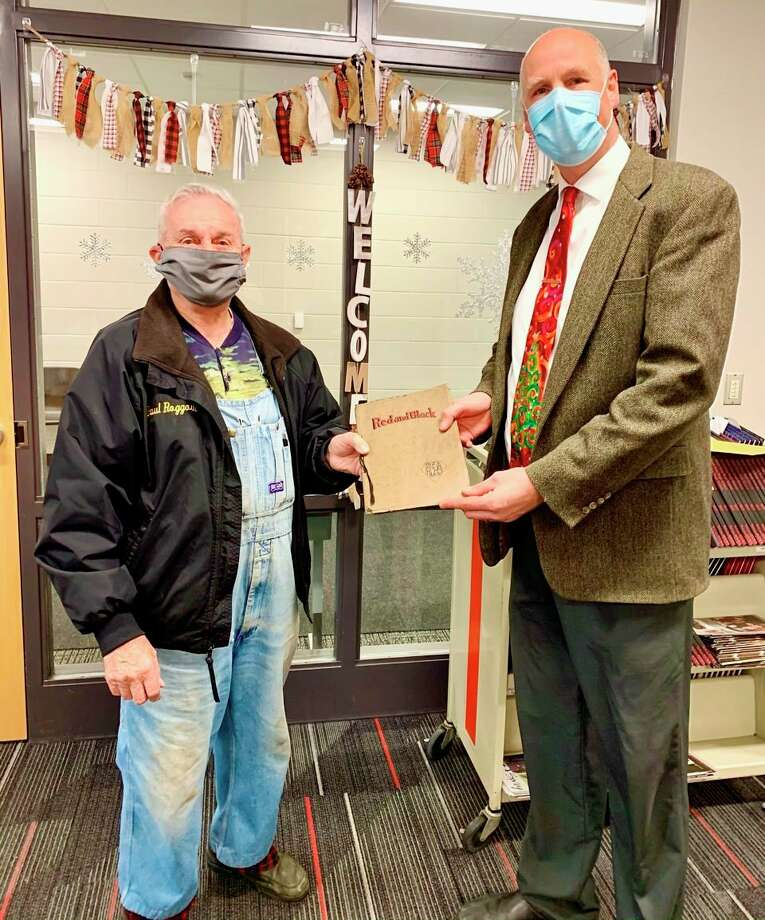 Reed City Superintendent Michael Sweet (right) hands over the 1923 Reed City High School yearbook to Old Rugged Cross Historical Museum staff. It will be preserved there for the rest of the community to see. (Courtesy photo)