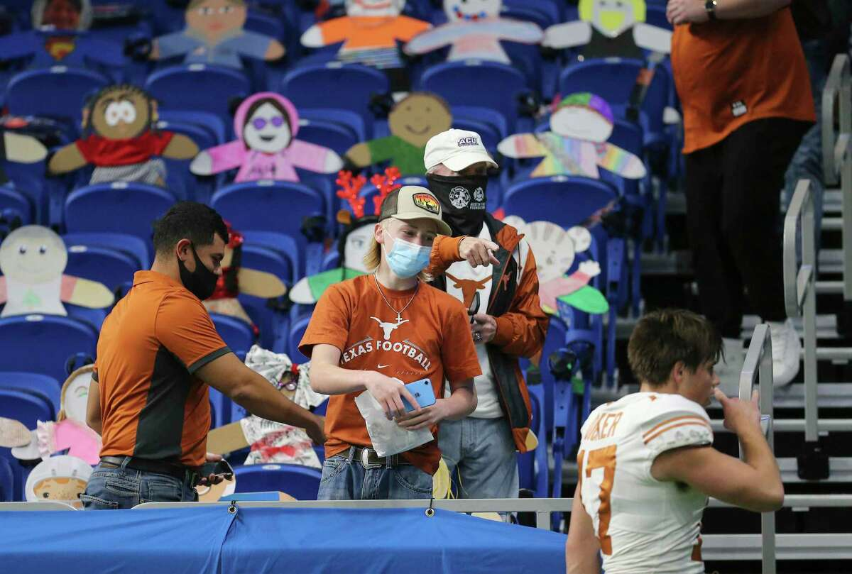Fans try to get the attention of Texas' Myles Mass (17) before the start of the 2020 Valero Alamo Bowl at the Alamodome on Tuesday, Dec. 29, 2020.