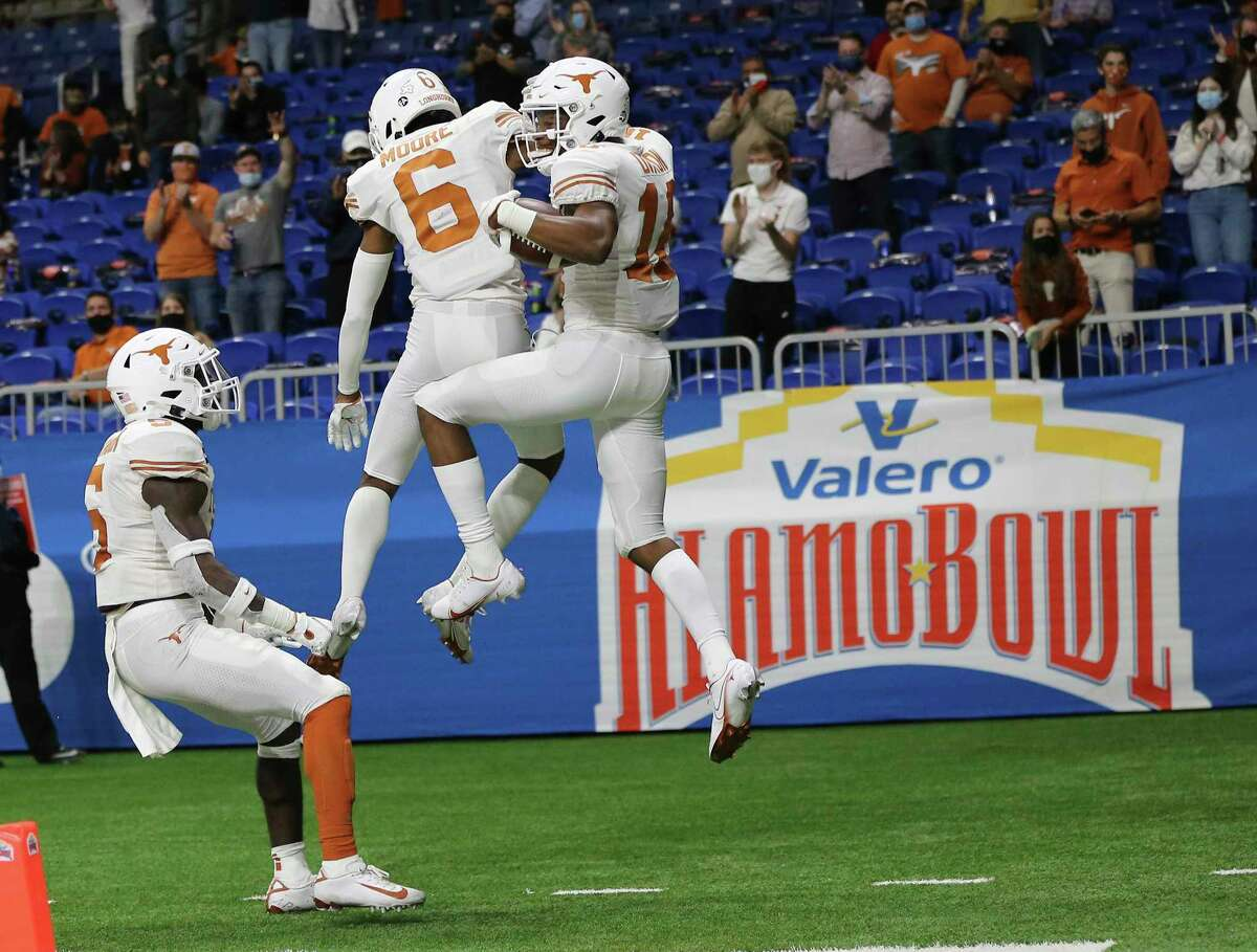 Texas receiver Kelvontay Dixon (16) celebrates his touchdown with teammate Joshua Moore (06) against Colorado in the fourth quarter during the 2020 Valero Alamo Bowl at the Alamodome on Tuesday, Dec. 29, 2020.