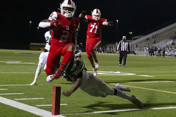 The Woodlands wide receiver Teddy Knox (2) leaps past Fort Bend Hightower defensive back Jeremy Strawder and over the pylon to score a 2-point conversion during the fourth quarter of a non-district high school football game at Woodforest Bank Stadium, Friday, Oct. 16, 2020, in Shenandoah.