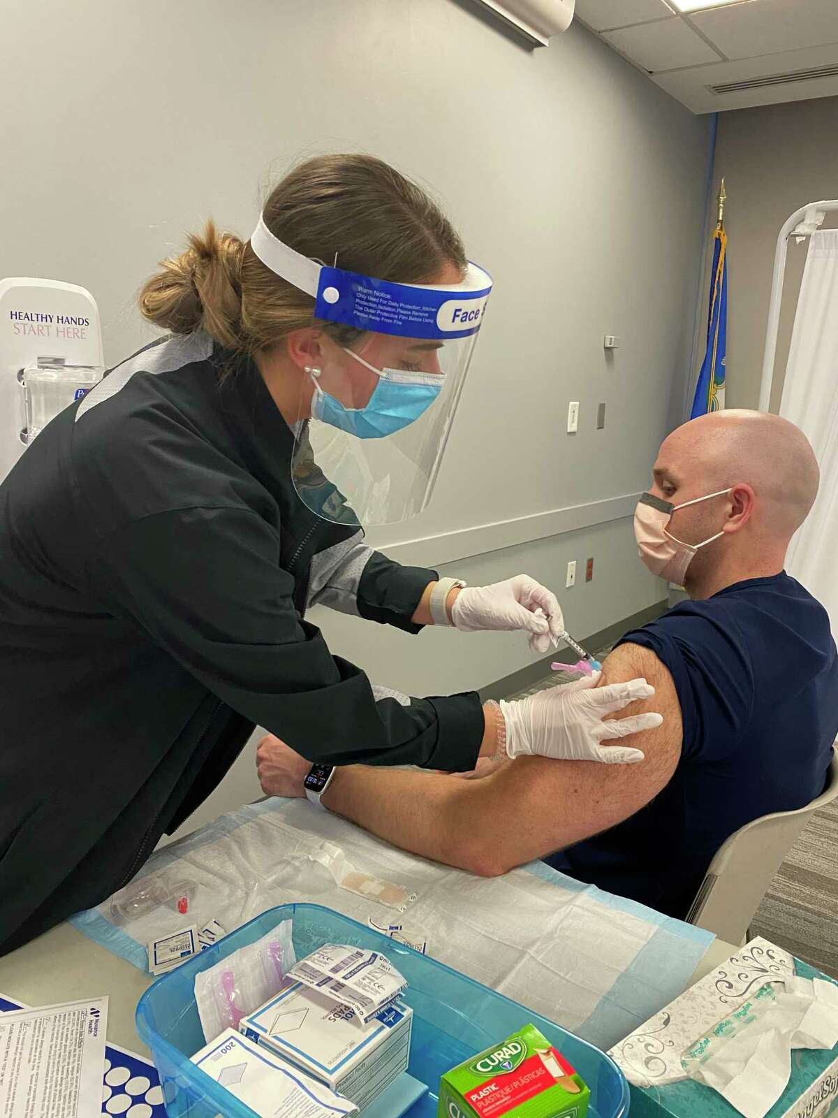 A Fairfield University nursing student vaccinating a healthcare worker.