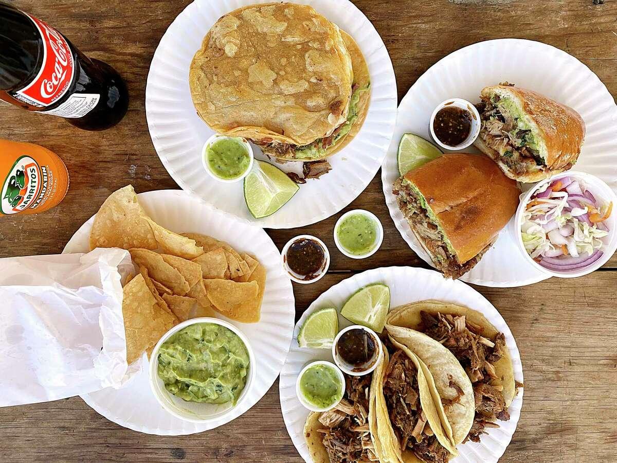 The menu at the food trailer Carnitas Don Raúl includes, clockwise from top, a quesadilla moreliana (carnitas, cheese, guacamole and beans), a torta moreliana (carnitas. cheese, guacamole and beans), carnitas tacos and guacamole.