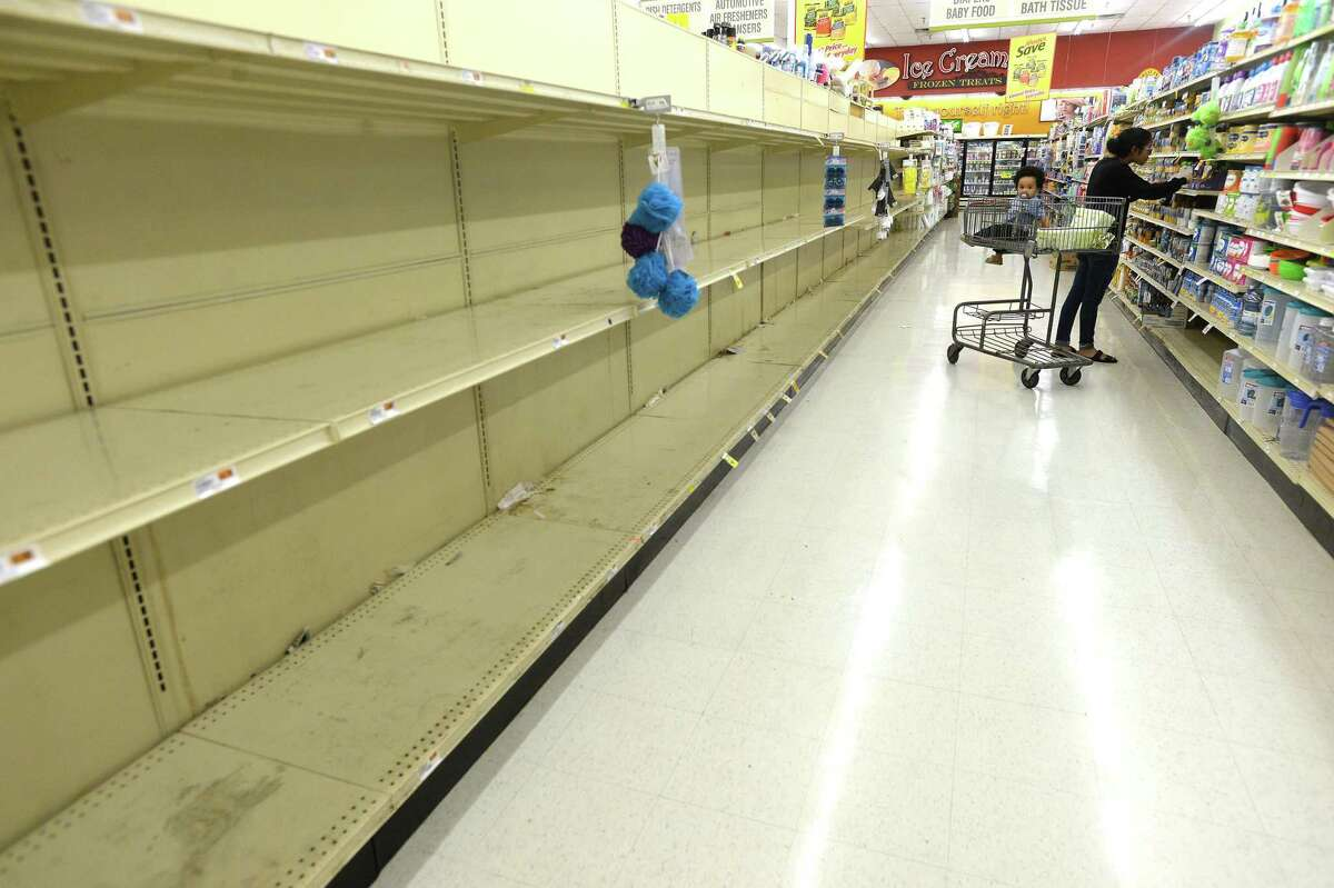 Shoppers stock up amid some barren and near-empty shelves of staples, especially toilet paper, paper towels, water and bread, at the Market Basket on Phelan and Major in Beaumont Friday as residents stock up in preparation for the potential spread of the coronavirus and quarantine conditions. Photo taken Friday, March 13, 2020 Kim Brent/The Enterprise