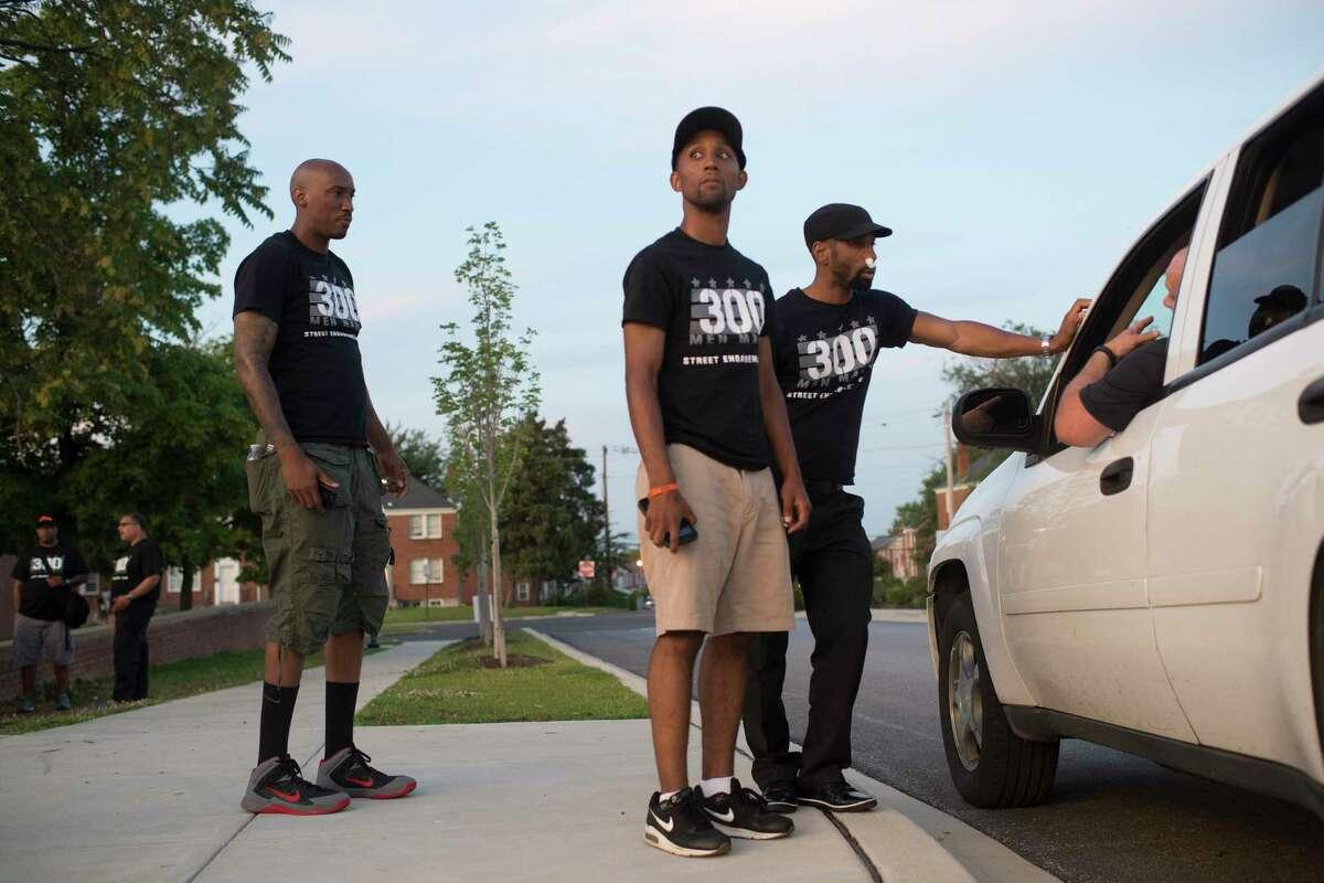 Ike Carter, left, Baltimore Council member Brandon Scott and Munir Bahar listen to a person warn them of recent gunshots in 2015.