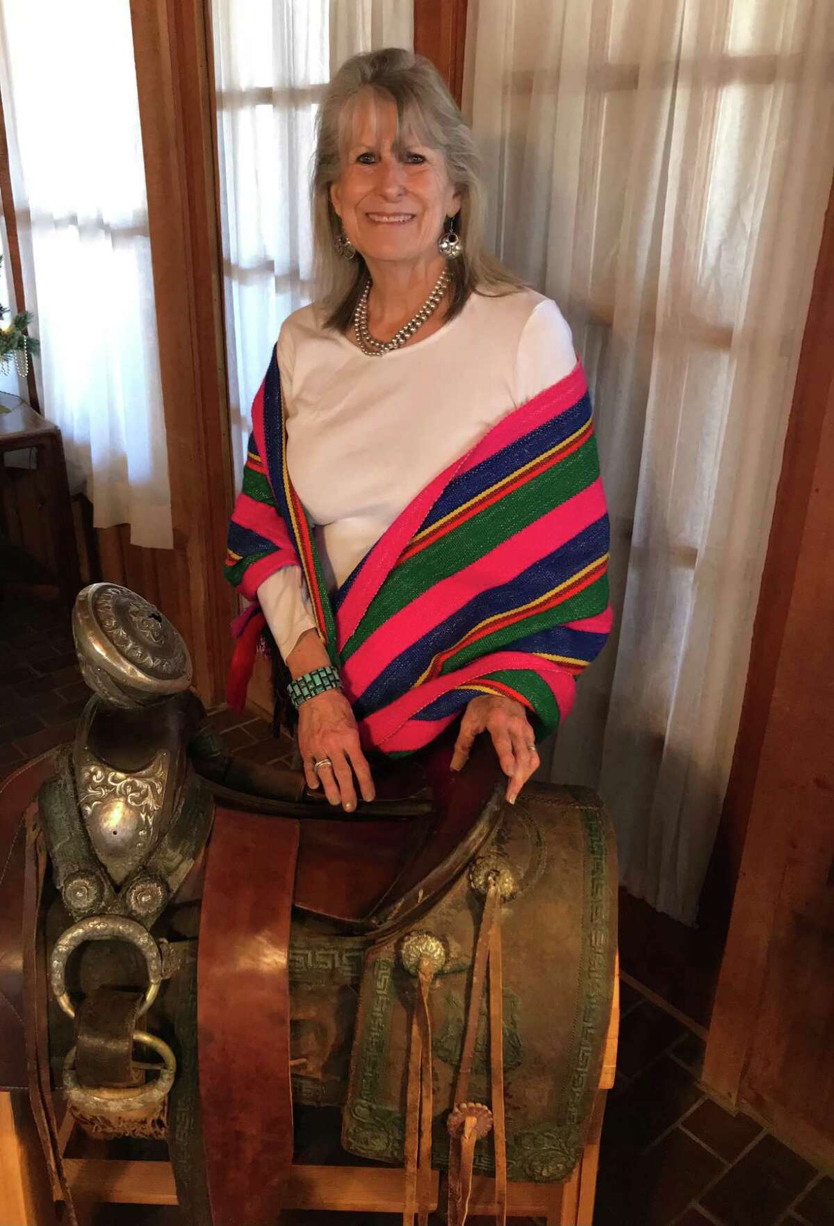 Wanda Garner Cash poses with Pancho Villa's saddle, which for many years resided in the Cadillac Bar dining room in Nuevo Laredo. Today it's in Cash's Hill Country home.