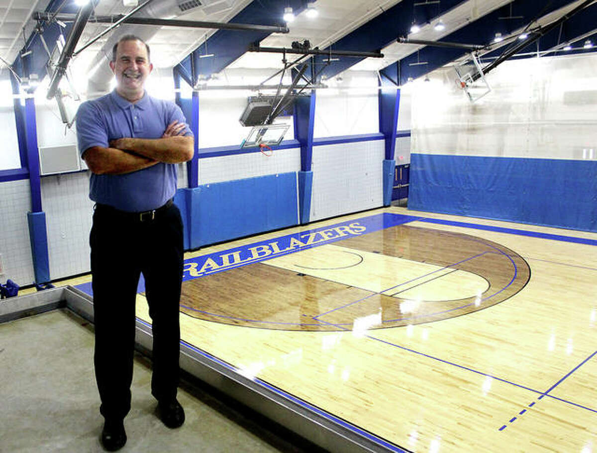 Lewis and Clark Community College athletic director Doug Stotler smiles with the River Bend Arena's new hardwood basketball/volleyball court in the background. Stotler, a member of the NJCAA Board of Regents, participated in the recent vote which added four sports to the NJCAA