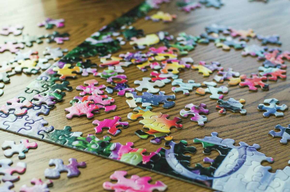 Pieces of ajigsaw puzzleare laid outon a table.(Photo by: GHI/Education Images/Universal Images Group via Getty Images)