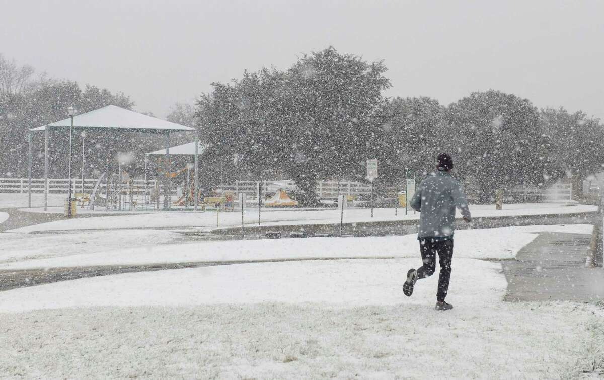 Heavy wet snow falls 12/30/2020 morning around Midland but can't stop a jogger at Cowden Park. Tim Fischer/Reporter-Telegram