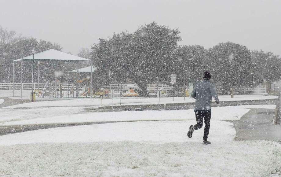 Heavy wet snow falls 12/30/2020 morning around Midland but can't stop a jogger at Cowden Park. Tim Fischer/Reporter-Telegram Photo: Tim Fischer, Midland Reporter-Telegram