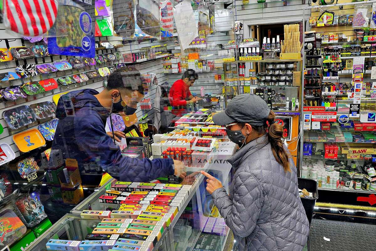 Saqr Abdulla helps Michelle Kelly purchase tobacco products at Evergreen Smoke Shop in Oakland. A law that would have taken effect on Jan. 1, a ban on flavored tobacco products, is on hold, pending a possible ballot measure.