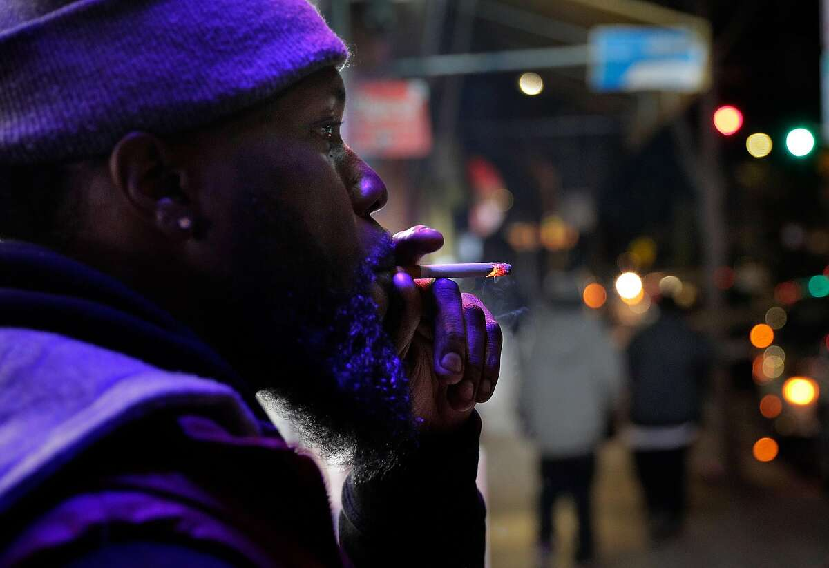 Malcolm Thompson smokes one of the Newports he purchased at Evergreen Smoke Shop in Oakland. A law that would have taken effect on Jan. 1, a ban on flavored tobacco products, is on hold pending a possible ballot measure.