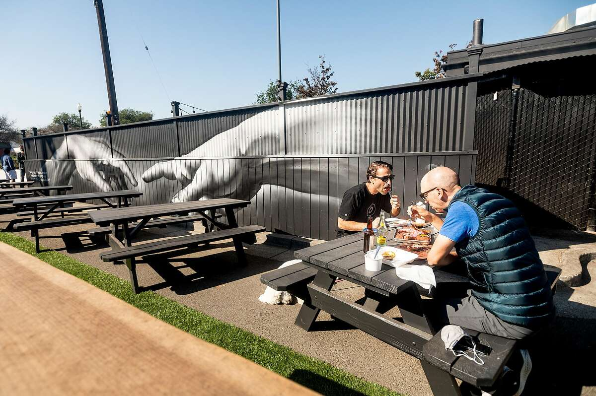 Dennis Pilarinos (left) and Mike Dauber eat at Horn Barbecue in Oakland in October 2020.