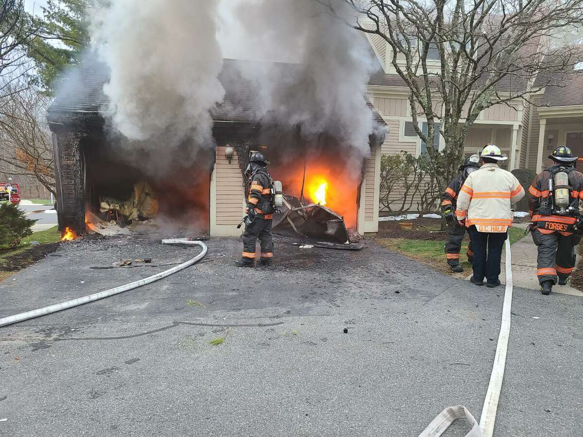 DANBURY, Conn. - firefighters battle a fire that tore through a garage at a townhouse complex on the city's northside Wednesday, Dec. 30 2020. One person was hospitalized in critical condition, a fire spokesman said.