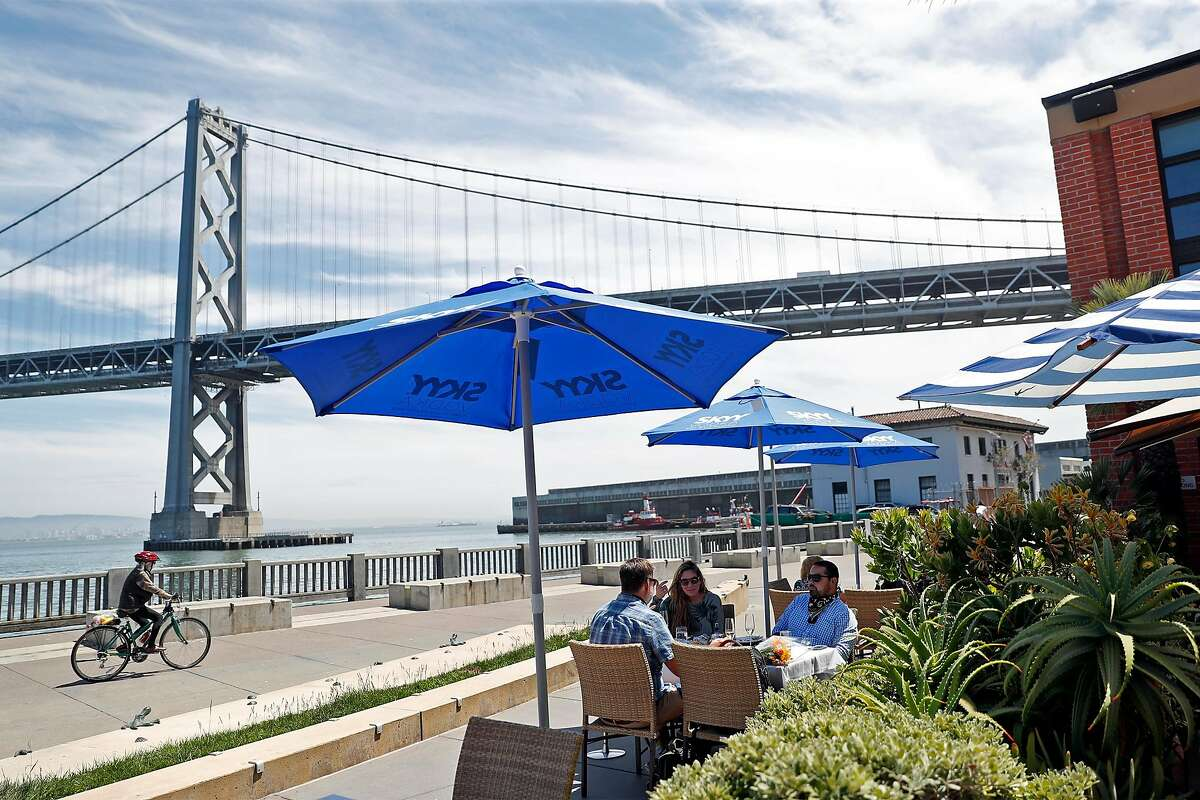 Todd Caine, Karen Dexter and Cyrus Dadci lunch at Waterbar in San Francisco in August. The restaurant has had umbrellas and outdoor heating lamps stolen from its property over the last few weeks while it has been closed.