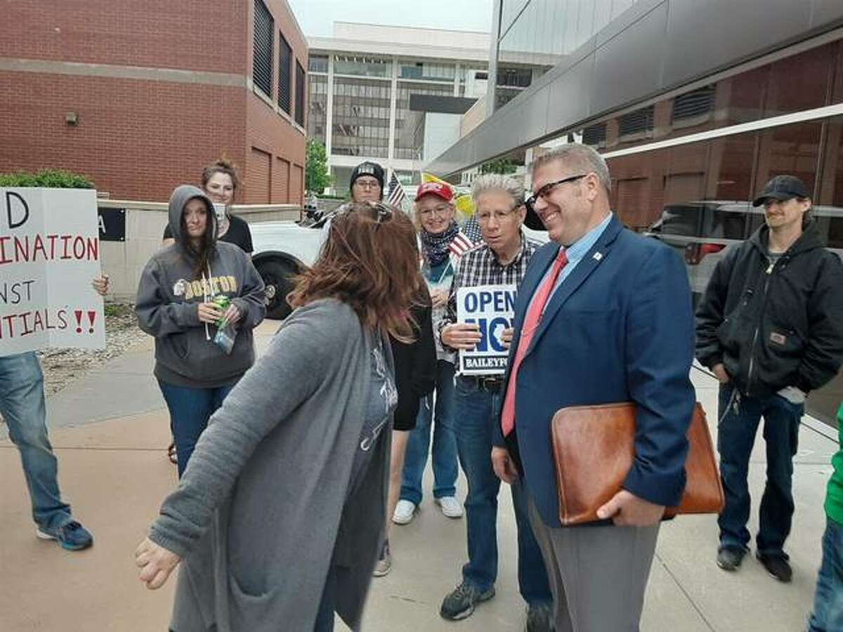 State Rep. Darren Bailey talks with protestors outside the Bank of Springfield Center after he was removed by a House vote for refusing to wear a face covering during the session going on inside the arena May 20.