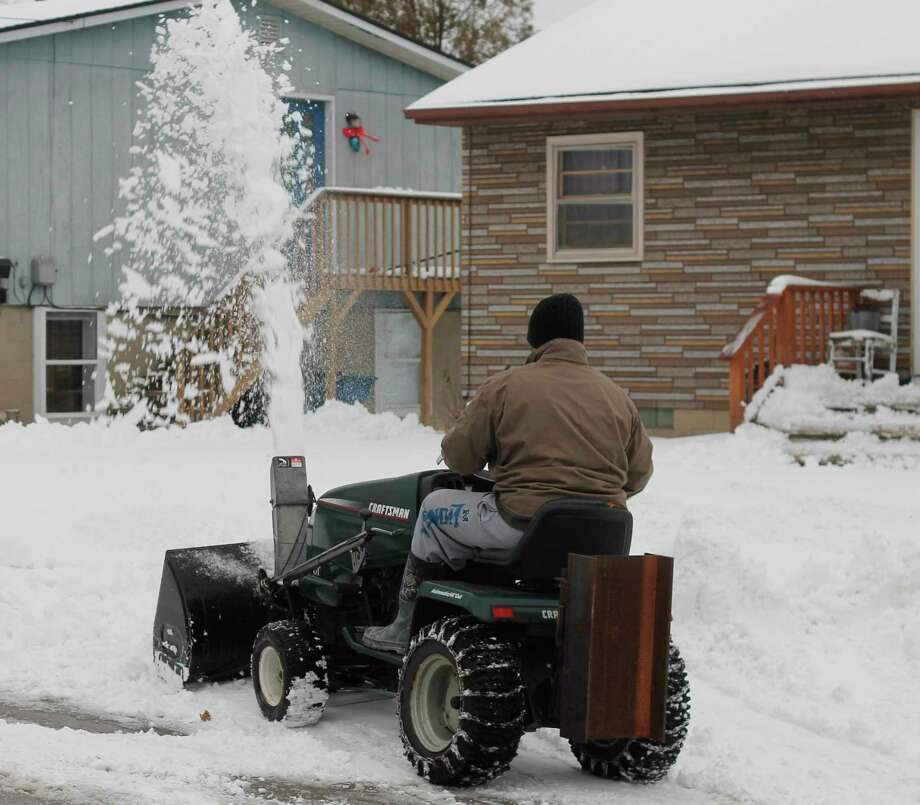 Northern Michigan residents brought out their snow blowers, salt and shovels Wednesday morning following a winter storm which hit the region overnight. (Kyle Kotecki/News Advocate)