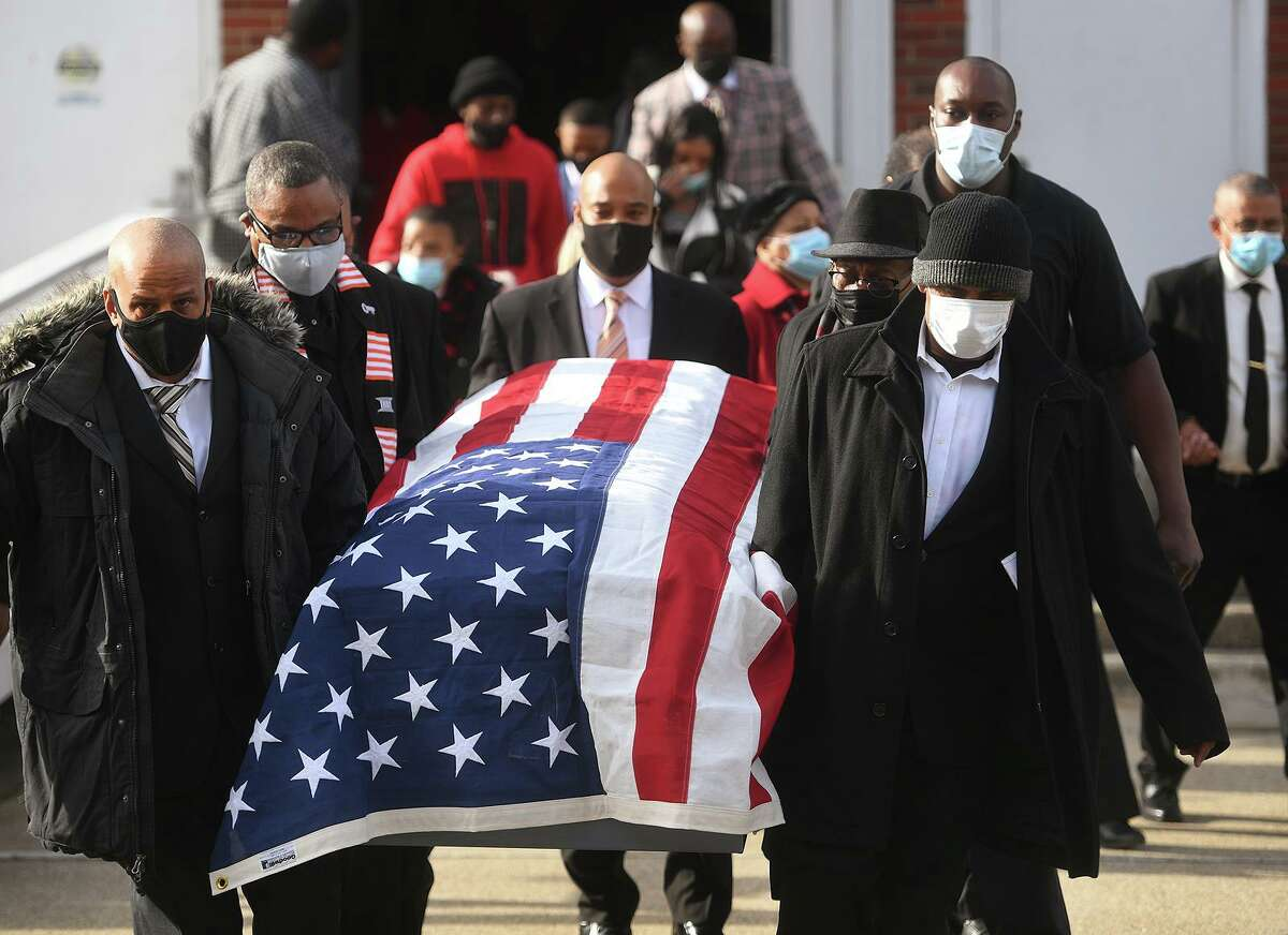 Draped in the American flag, the casket of State Senator Ed Gomes is carried from his funeral service at Blessed Sacrament RC Church on Union Avenue in Bridgeport, Conn. on Wednesday, December 30, 2020.